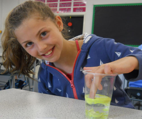 A student explores the properties of hydrophobic sand in the transition workshop from Thinkers in Education